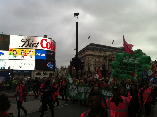 "The TUC ""Britain Needs A Pay Rise"" march passes Piccadilly Circus under grey skies"