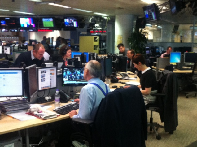 ITV News's Alastair Stewart consults with colleagues at a desk in the ITN London studio